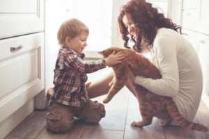 A kid and a woman playing with a cat