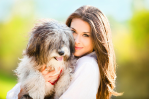 A Woman holding a pet dog in her arms
