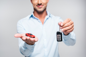 a man with a toy car in palm and holding car keys in other hand